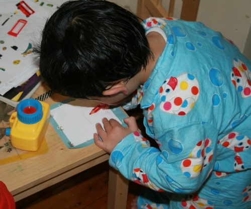 Child writing at table